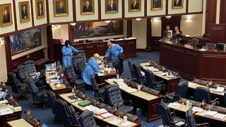 Crews in blue medical gowns swabbed the Florida House floor on March 9, 2020.