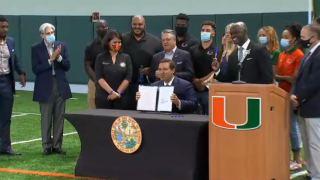 Florida Gov. Ron DeSantis signs a bill allowing college athlete compensation at the University of Miami on June 12, 2020.