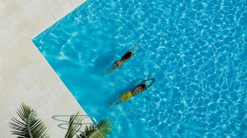 Aerial view of woman and man swimming in a pool - stock photo