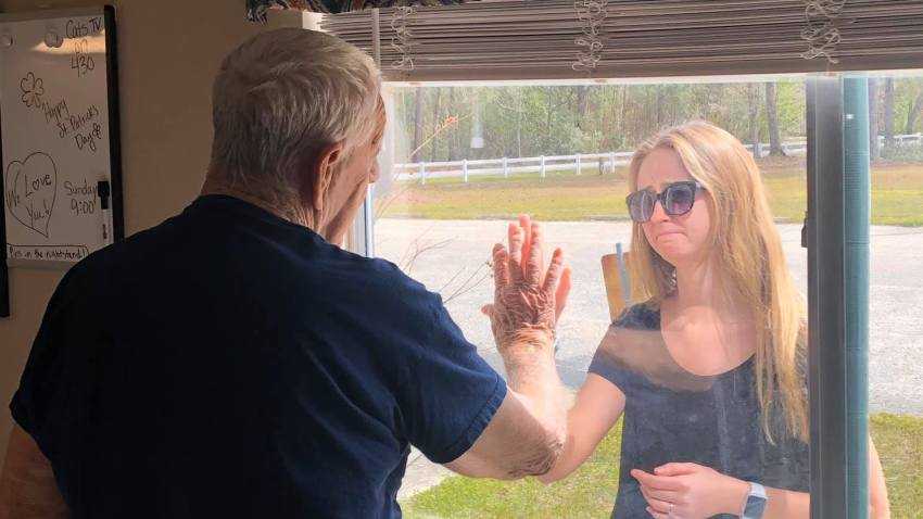 Carly Boyd shares the news of her engagement with her grandfather, Shelton, through the window of Premier Living and Rehab Center on March 16, 2020. The center is restricting all visitation amid the coronavirus pandemic.