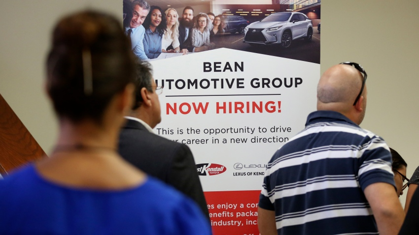 People stand in line to inquire about jobs available at the Bean Automotive Group during a job fair in Miami.