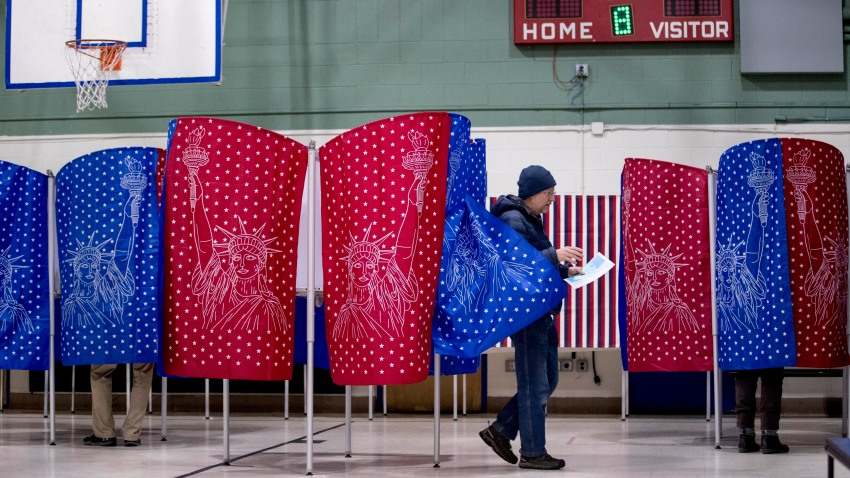 A man walks out of a voting booth during the New Hampshire Primary at Parker-Varney Elementary School, Tuesday, Feb. 11, 2020, in Manchester, N.H.