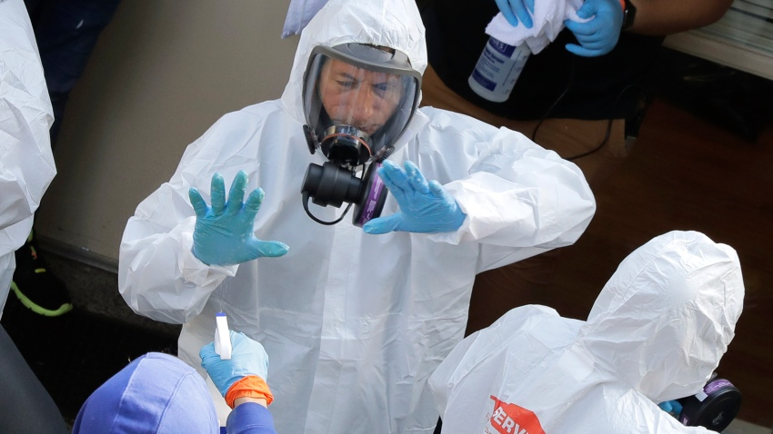 Servpro cleaning workers are sprayed as they exit the Life Care Center in Kirkland, Wash., Thursday, March 12, 2020, at the end of a day spent cleaning inside the facility near Seattle. The nursing home is at the center of the outbreak of the new coronavirus in Washington state.