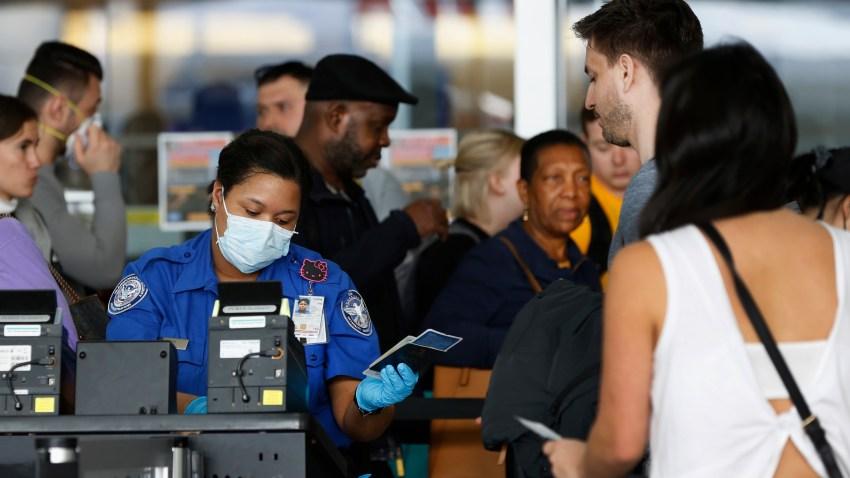 A TSA agent hands a passport back to a traveler as she screens travelers