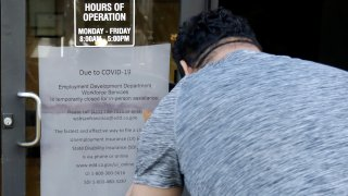 A man takes a photo of a sign advising that the Employment Development Department is closed due to coronavirus concerns, in San Francisco on Thursday, March 26, 2020.