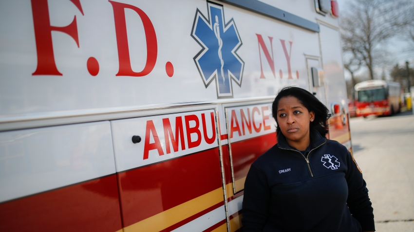 911 dispatcher stands next to ambulance