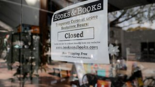 A sign on locally owned business Books & Books says the store is closed during the coronavirus pandemic, Thursday, April 9, 2020, in Miami.