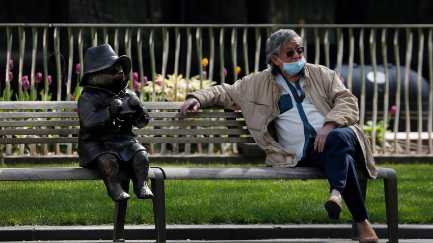 A man relaxes on a bench in London, next to a sculpture of Paddington Bear, as the country is in lockdown to help curb the spread of the coronavirus, Wednesday, April 15, 2020. The highly contagious COVID-19 coronavirus has impacted on nations around the globe, many imposing self isolation and exercising social distancing when people move from their homes.