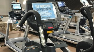A sign on posted on gym equipment, advises patrons to practice social distancing amid the COVID-19 virus outbreak at Bodyplex Fitness Adventure on Friday, April 24, 2020, in Grayson, Ga. Gov. Brian Kemp announced this week the resumption of elective medical procedures, as well as the reopening of certain close-contact businesses like gyms, barbershops and tattoo parlors.