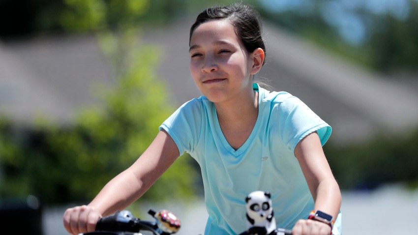 Juliet Daly, 12, rides her bike outside her home in Covington, La.