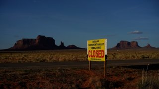 This April 23, 2020 photo shows a sign posted in Oljato-Monument Valley, Utah, saying the Navajo Monument Vally Tribal Park is closed, in an effort to prevent the spread of COVID-19 on the Navajo reservation. The reservation has some of the highest rates of coronavirus in the country.