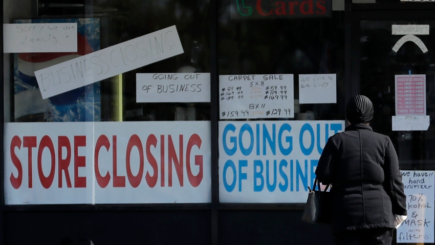 In this May 13, 2020, file photo, a woman looks at signs at a store closed due to COVID-19 in Niles, Ill.,