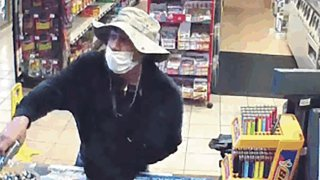 This image from surveillance video shows a man, believed to be William Rosario Lopez wearing a surgical mask, with a gun in a Connecticut convenience store