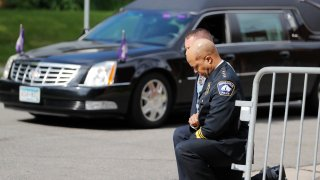 Police officers including Minneapolis Police Chief Medaria Arradondo, foreground, take a knee as the body of George Floyd arrives before his memorial services on Thursday, June 4, 2020 in Minneapolis.