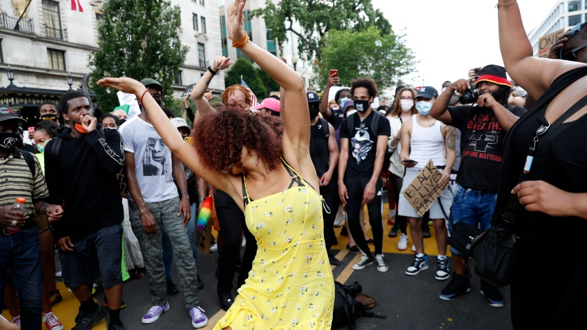 Demonstrators dance as they protest