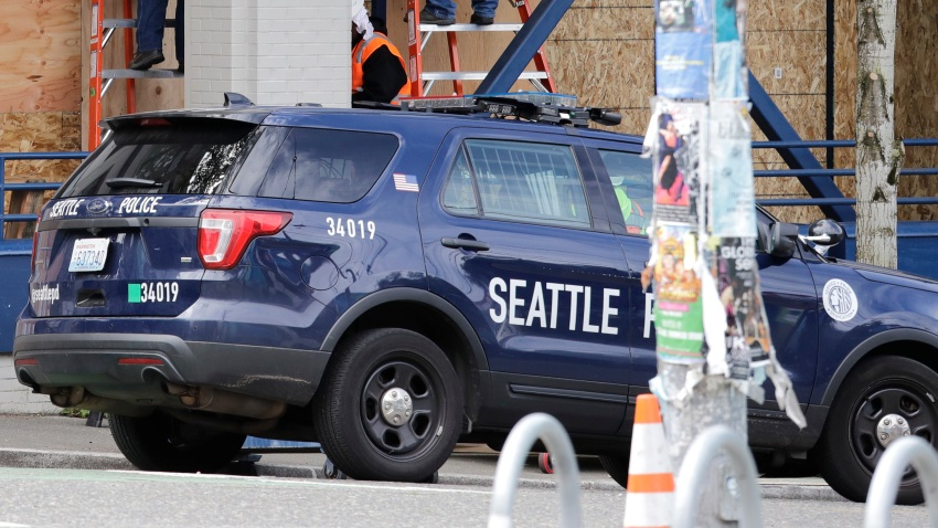 Workers put up plywood over the windows of a Seattle police precinct Monday, June 8, 2020, in Seattle