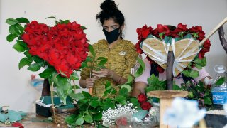 FILE - In this May 10, 2020, file photo, a merchant prepares a floral arrangement on Mother's Day at the Los Angeles Flower Market in Los Angeles. Americans are more unhappy today than they've been in nearly 50 years. That's according to the COVID Response Tracking Study, conducted in late May by NORC at the University of Chicago.