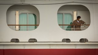 A worker wearing a protective mask cleans a handrail aboard the Carnival Corp. Miracle cruise ship anchored at the Port of Long Beach in Long Beach, California, April 13, 2020.