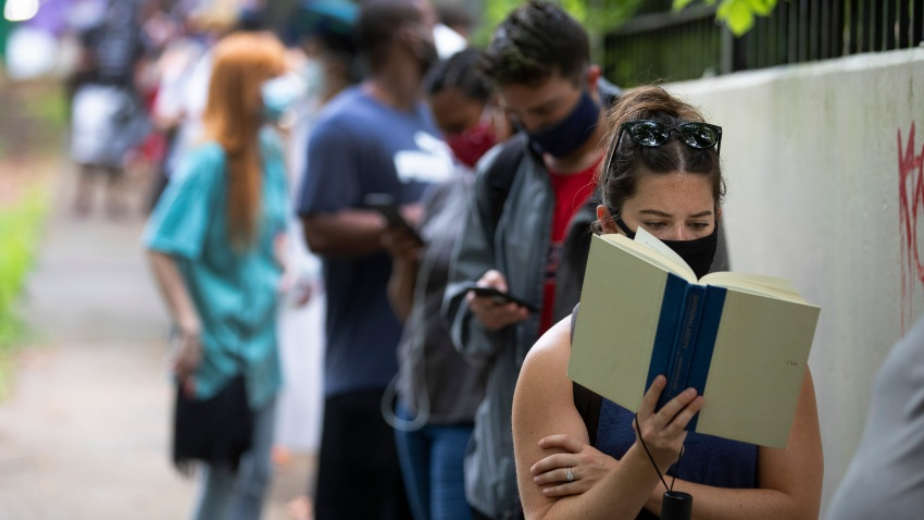 Kelsey Luker reads as she waits in line to vote, Tuesday, June 9, 2020, in Atlanta. Luker said she had been in line for almost two hours.