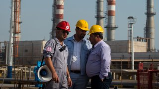 Employees stand near an Iranian national flag at the new Phase 3 facility at the Persian Gulf Star Co. (PGSPC) gas condensate refinery in Bandar Abbas, Iran