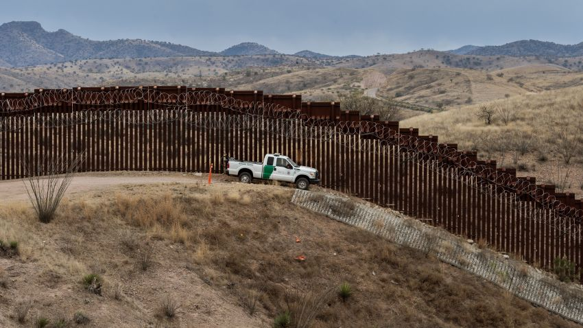 Border Patrol car in front of Arizona border wall