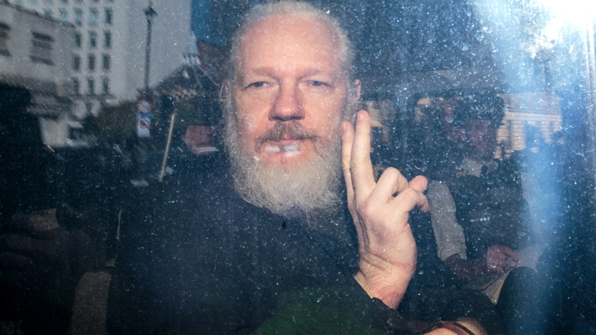 In this file photo, Julian Assange gestures to the media from a police vehicle on his arrival at Westminster Magistrates court on April 11, 2019 in London, England.