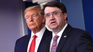 In this March 18, 2020, file photo, Robert Wilkie, U.S. Department of Veterans Affairs secretary, speaks while President Donald Trump, left, listens during a Coronavirus Task Force news conference in the briefing room of the White House in Washington, D.C.