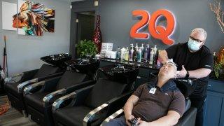 Harris Little washes Matt Kim's hair at 2Qute Hair Salon on April 27, 2020 in Atlanta, Georgia.