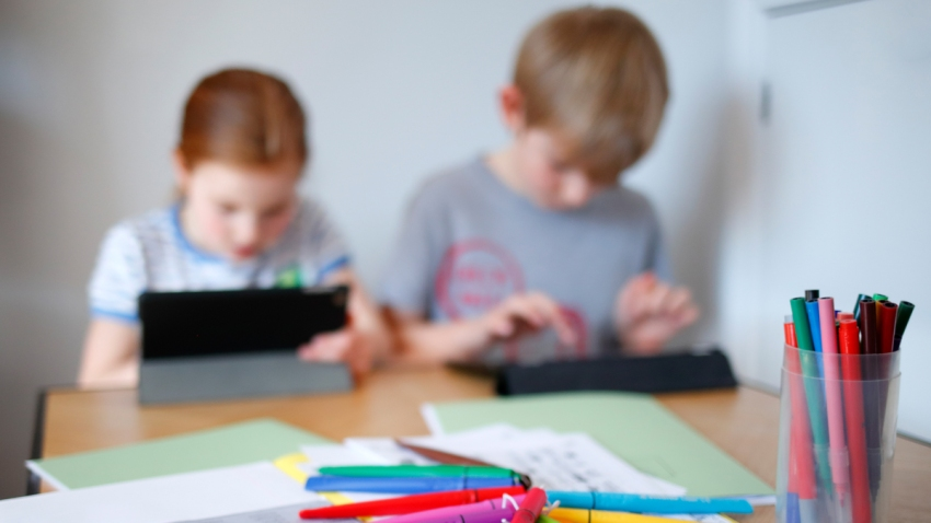 In this file photo illustration, children use iPads to complete online schoolwork at home amid the coronavirus pandemic on March 22, 2020 in Cuckfield, England.