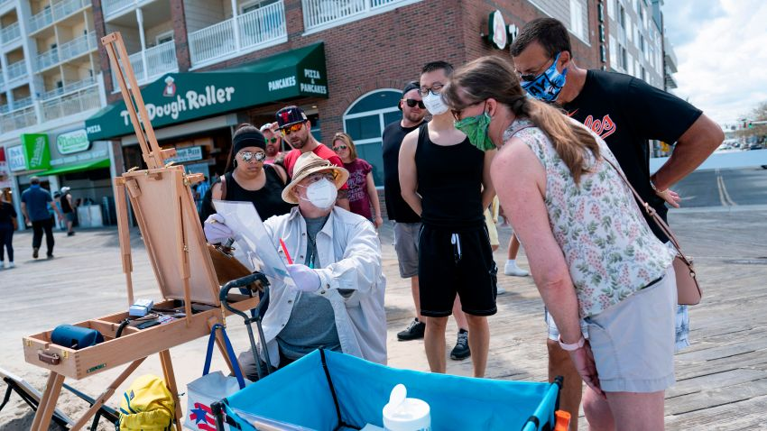 A local artist and onlookers wear masks on the boardwalk during the Memorial Day holiday weekend on May 23, 2020 in Ocean City Maryland. - The beach front destination has lifted its COVID-19 related beach and boardwalk restrictions May 9 and lodging restrictions May 14. The state of Maryland moved from a stay-at-home order to safe-at-home order May 15. (Photo by Alex Edelman / AFP) (Photo by ALEX EDELMAN/AFP via Getty Images)