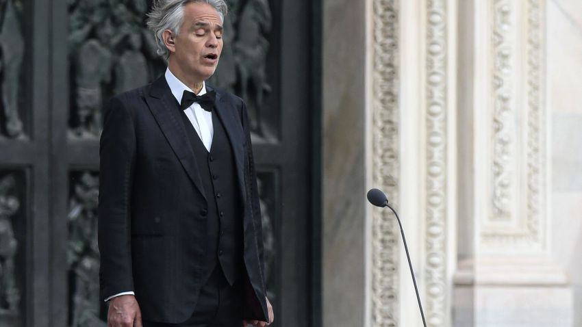 This photo taken on April 12, 2020 shows Italian tenor and opera singer Andrea Bocelli sing during a rehearsal on a deserted Piazza del Duomo in central Milan, prior to an evening performance without public for the world wounded by the pandemic, during the country's lockdown aimed at curbing the spread of the COVID-19 infection, caused by the novel coronavirus.