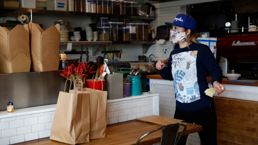 Yuka Ioroi, co-owner of Cassava restaurant on Balboa Street, manages take-out orders in San Francisco, Calif. on Wednesday, April 8, 2020.