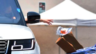 A driver drops off her coronavirus test at a COVID-19 testing site in Los Angeles on June 24, 2020.