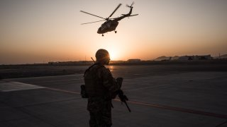 U.S. soldier watches a helicopter in Afghanistan