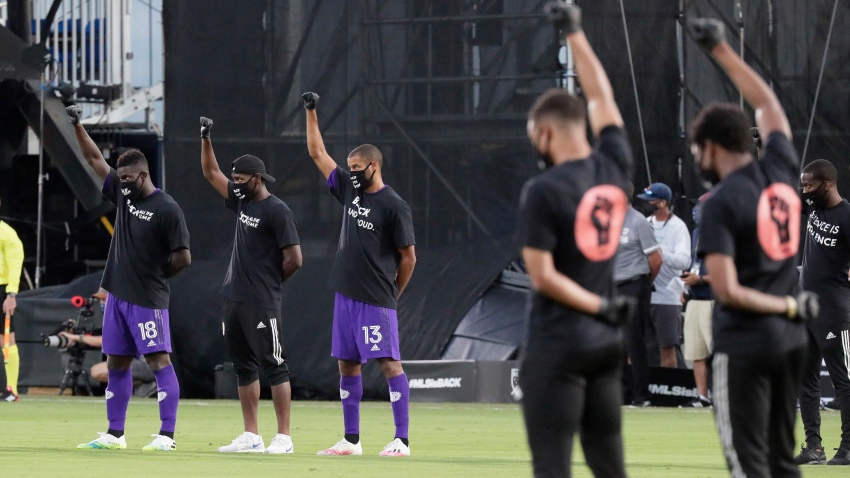 Orlando City players, left, raise their fists in the air in solidarity with other MLS teams before the start of an MLS soccer match, Wednesday, July 8, 2020, in Kissimmee, Fla., while wearing shirts and masks with messages about race.