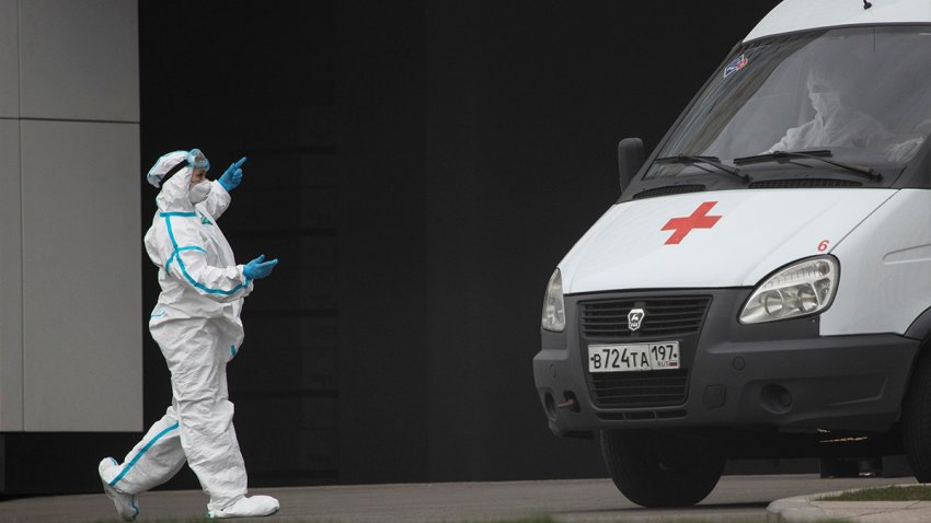 A medical worker wearing protective gear directs an ambulance at a hospital for coronavirus patients, April 27, 2020, in Kommunarka, outside Moscow, Russia.