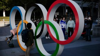 In this Feb. 23, 2020, file photo, people wait in line to take pictures with the Olympic rings near the New National Stadium in Tokyo, Japan.