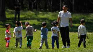 In this May 11, 2020, file photo, children accompanied by a man play at a public park as kindergarten and primary schools remain closed following the coronavirus outbreak in Beijing, China.