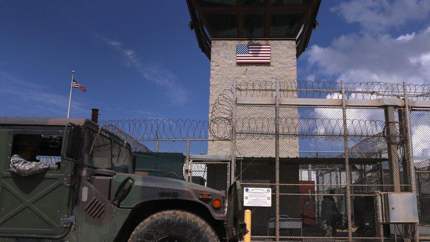 "A humvee passes the guard tower guard tower at the entrance of the U.S. prison at Guantanamo Bay, also known as ""Gitmo"" on October 23, 2016 at the U.S. Naval Station at Guantanamo Bay, Cuba."
