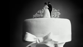 Figurines of a woman in a wedding dress and a man wearing a suit stand atop a wedding cake with their backs turned toward the camera.