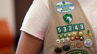 In this June 18, 2018, file photo, the vest of a Girl Scout is seen filled with badges and awards at a demonstration of some of their activities in Seattle.