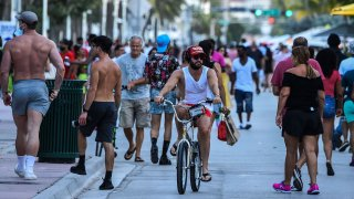 A man rides a bicycle as people walk on Ocean Drive in Miami Beach, Florida on June 26, 2020.