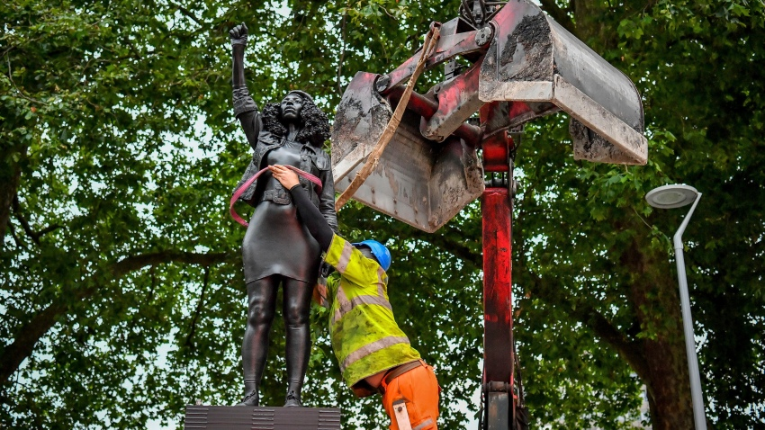 "A contractor uses ropes to secure the statue ""A Surge of Power (Jen Reid) 2020"" by artist Marc Quinn, which had been installed on the site of the fallen statue of the slave trader Edward Colston, as they prepare to remove and load it into a recycling and skip hire lorry, in Bristol, Thursday, July 16, 2020. The sculpture of protestor Jen Reid was installed without the knowledge or consent of Bristol City Council and was removed by the council 24 hours later."