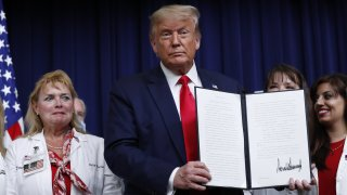 U.S. President Donald Trump holds an executive order on lowering drug prices after being signed during a ceremony in the Eisenhower Executive Office Building in Washington, D.C., U.S., on Friday, July 24, 2020. Trump announced new policies aimed at lowering prescription drug prices under Medicare by linking them to rates paid in other countries and allowing Americans to buy prescription medication imported from Canada.