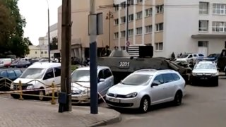 In this image take from video, the scene as streets are closed off, with an armored security vehicle and police car, right, after an armed man seized a bus and took some 20 people hostage in the city centre of Lutsk, some 400 kilometers (250 miles) west of Kyiv, Ukraine on Tuesday July 21, 2020.