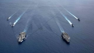 In this photo provided by U.S. Navy, the USS Ronald Reagan (CVN 76) and USS Nimitz (CVN 68) Carrier Strike Groups steam in formation, in the South China Sea, July 6, 2020.