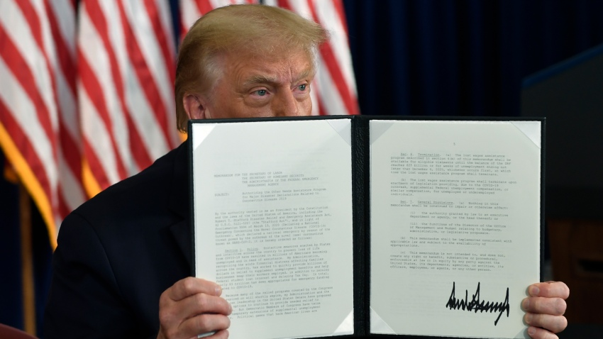 In this Aug. 8, 2020 file photo, President Donald Trump signs an executive order during a news conference at the Trump National Golf Club in Bedminster, N.J.