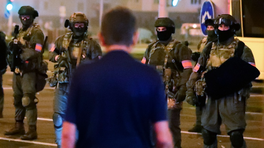 A protester stands in front of armed police during a mass protest following presidential elections in Minsk, Belarus
