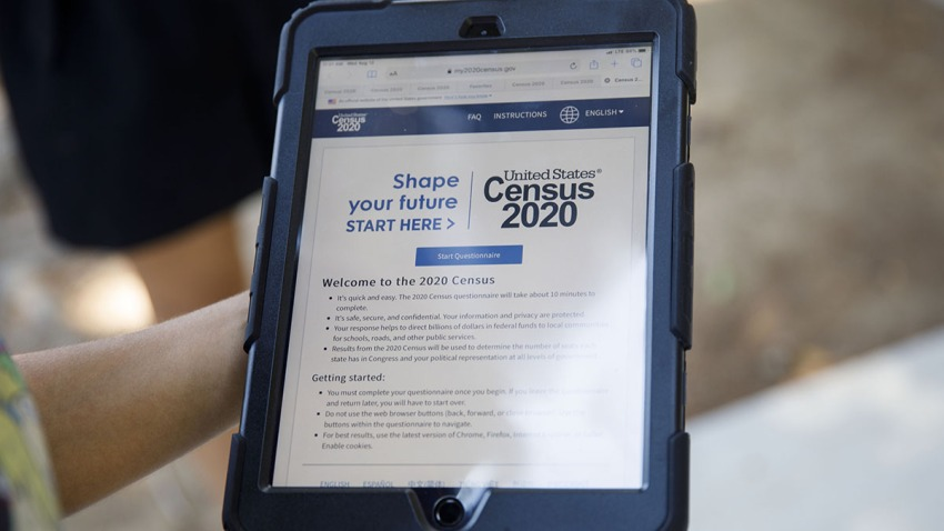 A YMCA youth ambassador holds a tablet with a Census 2020 interview questionnaire during a community food distribution in Los Angeles, Aug. 12, 2020.
