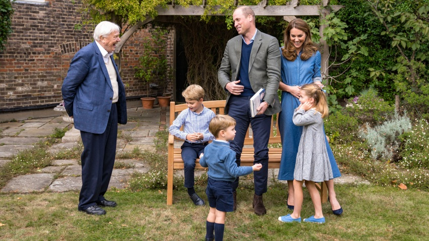 Britain's Prince William, centre, and Kate, the Duchess of Cambridge, react with Naturalist David Attenborough, left, with their children, Prince George, seated, Princess Charlotte, right and Prince Louis, foreground, in the gardens of Kensington Palace
